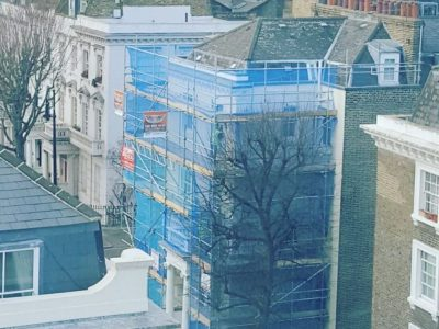 picture of a scaffolding with blue mesh sheeting erected around residential building