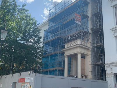 picture of a scaffolding with blue mesh sheeting erected on front of residential building